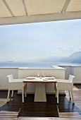 Laid table on terrace with sea view (Casa Angelina, Italy)