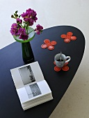 Book, cup of coffee and vase of flowers on designer table