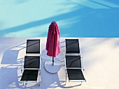 Loungers and sunshade by swimming pool