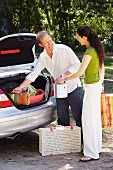 Couple packing picnic things into car boot