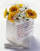 Original menu written on paper bag filled with flowers