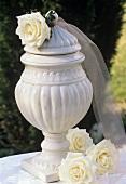 Rosen der Sorte 'Maroussia' neben antik anmutender Vase