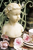 Bust of girl beside crockery and roses