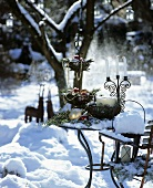 Weihnachtlich dekorierter Tisch in verschneitem Garten