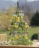 Iron stand with glasses filled with narcissi & twigs