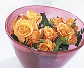 Bouquet of roses & pistachio foliage in a glass bowl