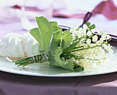 Posy of lilies-of-the-valley and meringue on a plate