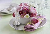 Bellis, tulips and narcissi in a coffee cup
