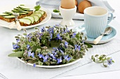 Borage wreath on breakfast table with egg & cucumber on bread