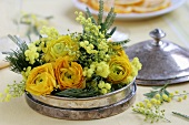 Arrangement of ranunculus and mimosa in a silver dish