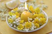 Brennende Kerze mit Blütenkranz