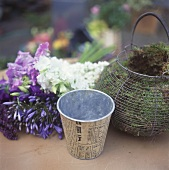 Basket of moss, metal cache-pot and flowers