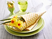 Easter place-setting with narcissi and fabric napkin