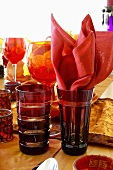 Red glasses, one with fabric napkin, on laid table