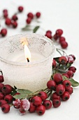 Frosted glass with candle and wreath of haws