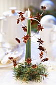 Christmassy table decoration with a candle and star anise