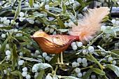 Orange glass bird among mistletoe