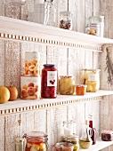 Storage shelf with preserving jars and tinned fruit