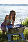 Junge Frau zündet Grill am See an