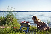 Junge Frau grillt am See