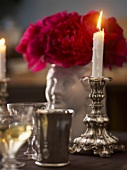 Candle in candlestick with roses and glasses