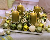 Advent arrangement: mistletoe, Christmas baubles, angel hair tinsel