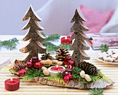 Christmas decoration: wooden fir trees, cones, baubles, candle