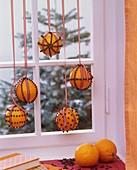 Mit Nelken gespickte Orangen hängen vor einem Fenster
