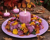 Wreath of chrysanthemums & cotoneaster with candle on plate