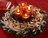Advent wreath of twigs, ivy and cranberries with candles