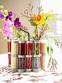 Various smoothies in test tubes with floral decoration