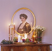 Chest of drawers with Christmas decorations and portrait