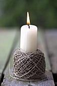 Brennende Kerze in einer Garnrolle
