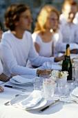 Freunde sitzen an festlich gedecktem Tisch mit Champagner