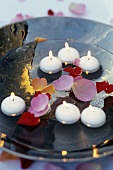 Floating candles and rose petals in a bowl