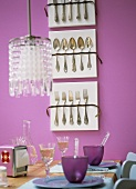 Laid table, display of cutlery on pink wall
