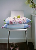 Coloured pillows with a pear on chair