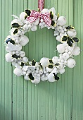 White Christmas wreath hanging on turquoise wooden wall