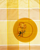 Orange rose on glass plate on checked tablecloth