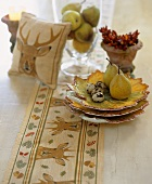 Pears, quails' eggs and autumnal decorations on table
