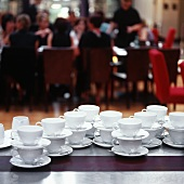 Many coffee cups on a table at a party