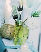 Sommerlich gedeckter Tisch mit Besteck und Serviette im Glas