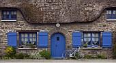 Steinhaus mit Reetdach und blaue Fensterrahmen
