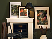 Fireplace with white cornice and table lamps in front of framed pictures of flowers on the wall
