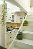 House plants on a white staircase in front of a country style kitchen with open floor plan