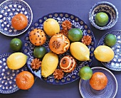 Still life with clove-studded oranges & other citrus fruit