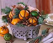 Bowl of citrus fruit studded with cloves, spices & greenery