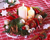 Arrangement of apples, fir sprigs, moss and baubles
