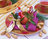 Schokoladennikoläuse mit Apfel und Erdnüssen als Tellerdeko