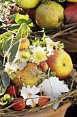 Gesteck mit verschiedenen Äpfeln, Apfelblüten und Rosen